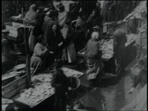 vídeos de stock e filmes b-roll de b/w 1903 newsreel high angle pan immigrants + pushcarts at ghetto fish market in lower east side / nyc - 1903