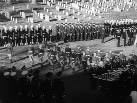 B/W 1963 high angle Irish honor guards lowering guns at JFK's funeral / US military in background / Arlington
