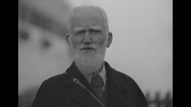 """high angle irish playwright and activist george bernard shaw surrounded by reporters at train station / sot shaw says """"i can't say that i'm very glad... - scriptwriter stock videos & royalty-free footage"""