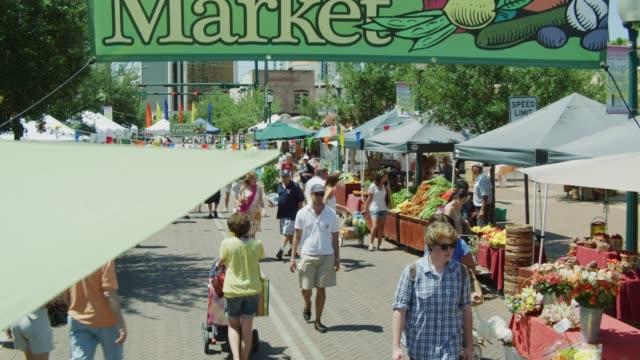 "high angle jib shot featuring a banner ""farmers market "" vendor tents flowers and customer activity on the busy city street. - jib shot stock videos & royalty-free footage"