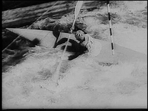 b/w 1966 high angle kayaker going into wall backwards in slalom competition on rapids / germany / newsreel - 若い男性だけ点の映像素材/bロール