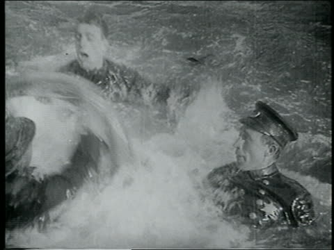 stockvideo's en b-roll-footage met b/w 1915 high angle keystone kops holding on to tires + struggling to swim in water / feature - 1915