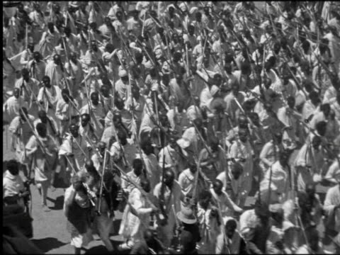 b/w 1930 high angle large crowd of men in white robes carry rifles + run in street / abyssinia -now ethiopia - ethiopia stock videos and b-roll footage