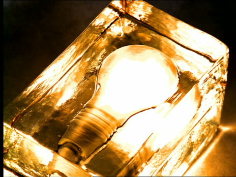 high angle large golden light bulb lighting + going out - inquadratura dall'alto di un tavolo video stock e b–roll