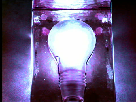blue high angle large light bulb lighting up + going out - inquadratura dall'alto di un tavolo video stock e b–roll