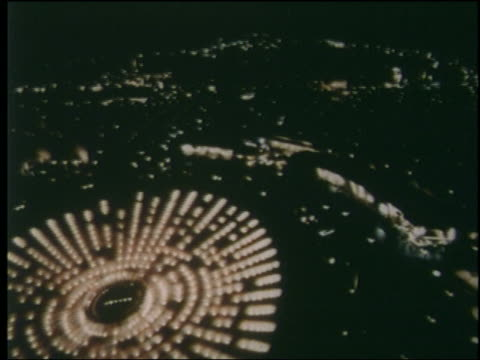 1964 high angle pan lights of ny world's fair in circular pattern at night - esposizione universale di new york video stock e b–roll