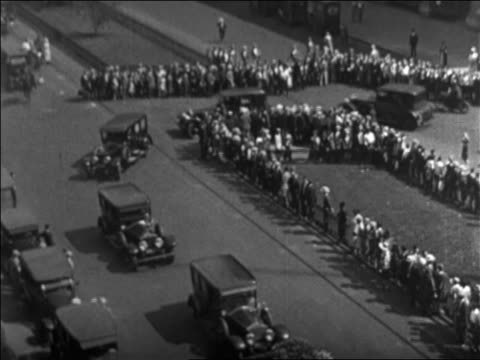 b/w 1926 high angle line of cars rounding corner in funeral procession for rudolph valentino / newsreel - 1926 stock videos & royalty-free footage