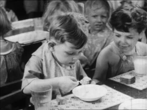 b/w 1934 high angle little boy eating in nursery school / wpa project / newsreel - schulkind nur jungen stock-videos und b-roll-filmmaterial