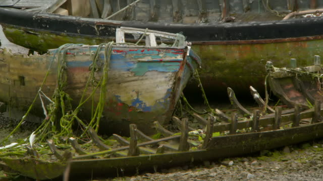 high angle lockdown shot of abandoned damaged boat moored on shore - galway, ireland - weathered stock videos & royalty-free footage