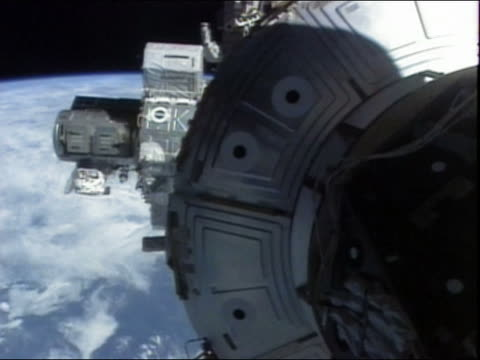 high angle long shot astronaut climbing out of a hatch on the international space station - heckklappe teil eines fahrzeugs stock-videos und b-roll-filmmaterial