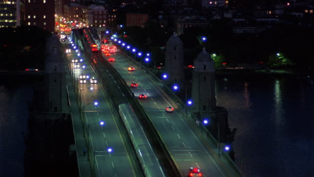 High angle long shot cars and train travelling over the Longfellow Bridge at night / Boston