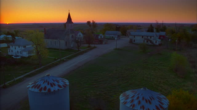 high angle long shot church and other buildings along road in small town / dusk or dawn - 1995 stock videos & royalty-free footage