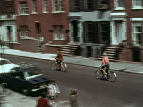 1969 high angle long shot pan couple riding bicycles past apartment buildings on city street / greenwich village - greenwich village stock videos & royalty-free footage