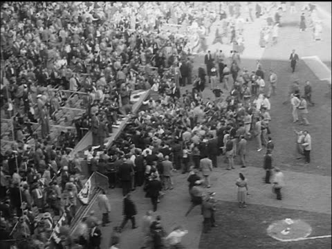 high angle long shot crowd surrounding brooklyn dodgers dugout at end of world series / nyc - 1955 stock-videos und b-roll-filmmaterial