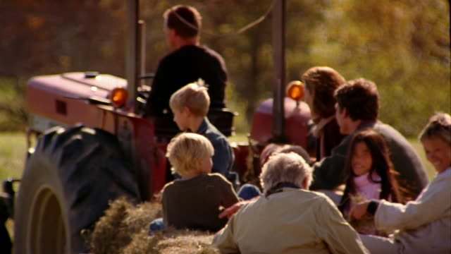high angle long shot family taking hayride in wagon being pulled by tractor - hay stock videos and b-roll footage
