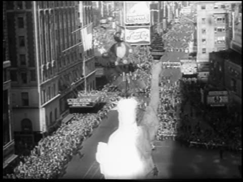 B/W 1945 high angle long shot giant balloons crowds at Macy's Thanksgiving Day parade / NYC / newsreel
