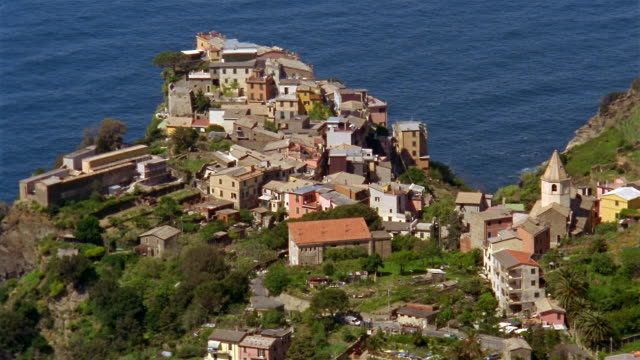 high angle long shot hilltop coastal village of corniglia with mediterranean sea in background / cinque terre, italy - mediterranean culture stock videos & royalty-free footage