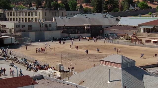 high angle long shot inmates walking and exercising in prison yard / california - prisoner stock videos & royalty-free footage