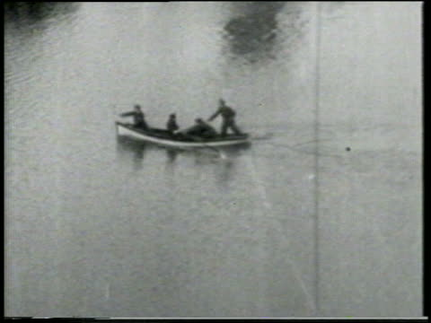 stockvideo's en b-roll-footage met b/w 1915 high angle long shot keystone kops rowing quickly across water / feature - 1915