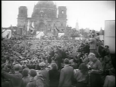 b/w 1950 high angle long shot large crowd of people watching marching in communist demonstration / berlin - 1950年点の映像素材/bロール