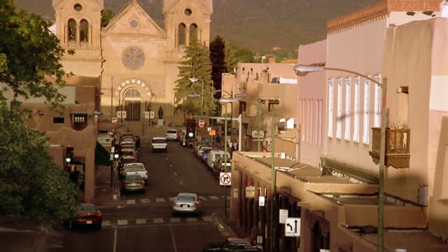 High angle long shot light traffic on San Francisco St. / tilt up view of Saint Francis Cathedral / Santa Fe, New Mexico