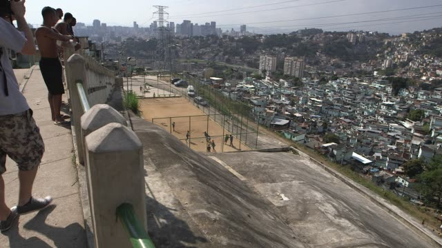 High Angle Long Shot local residents are watching the young boys football training from a terrace above the football pitch Children of the Morro da...
