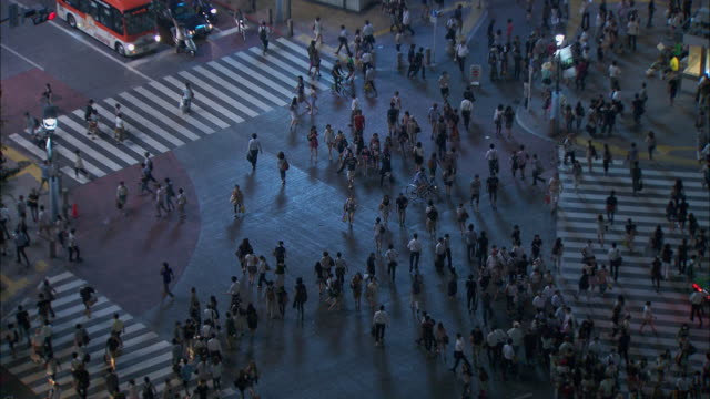 high angle long shot of hundreds of people using a road crossing in the city of nagasaki.  - crossing stock videos & royalty-free footage