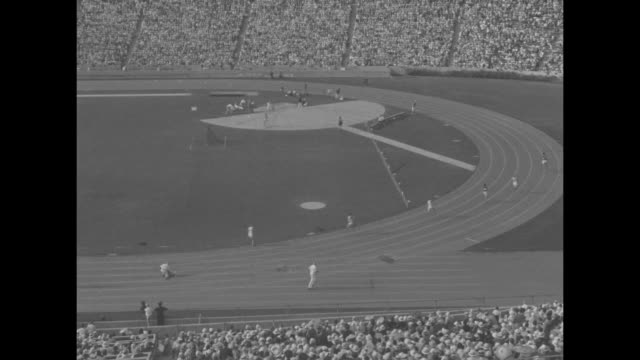 High angle long shot of Olympic runners at starting lines for men's 1600meter relay as crowd looks on from stands / pan as runners take off / runners...