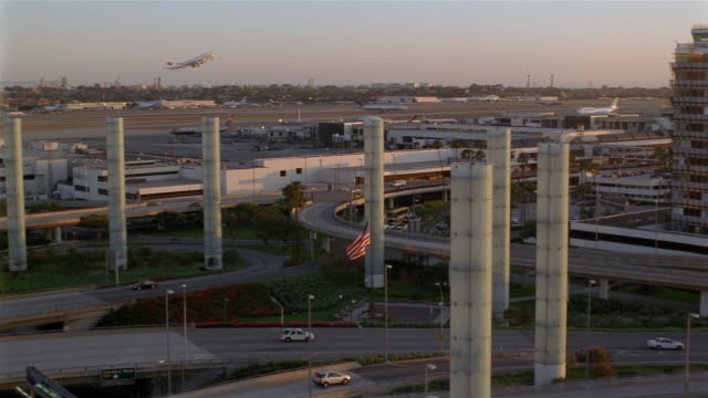 High angle long shot pan pylons at LAX / airplane taking off in background / Theme Building and control tower / Los Angeles