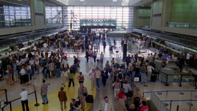 high angle long shot passengers standing in lines and walking through terminal at lax / los angeles - コンコース点の映像素材/bロール