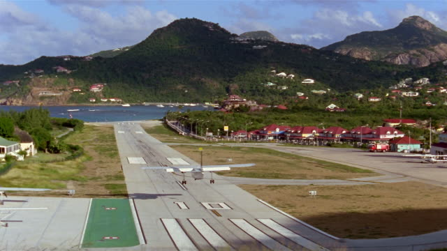 high angle long shot plane landing at airport / st. barthelemy, french west indies - landefahrwerk stock-videos und b-roll-filmmaterial