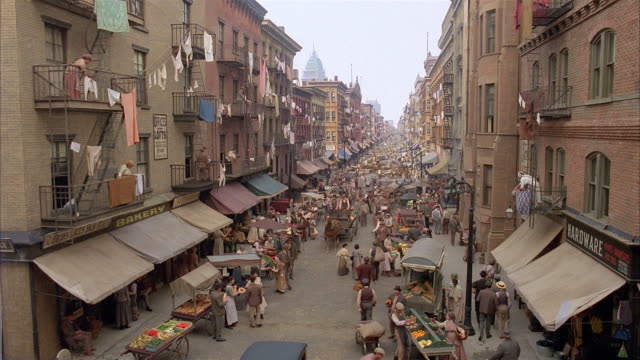 high angle long shot recreation of early 20th century new york city street scene / pedestrians and vendors on street - market reenactment stock videos & royalty-free footage