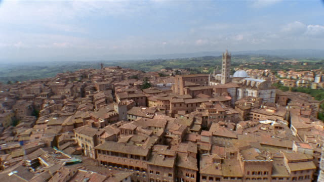 high angle long shot rooftops of houses and the duomo in siena / tuscany, italy - periodo medievale video stock e b–roll