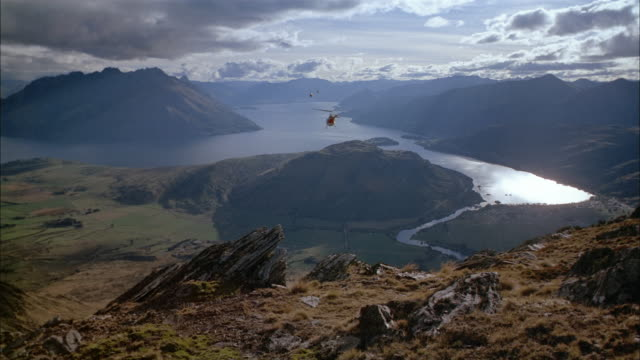 vidéos et rushes de high angle long shot six helicopters flying over mountain towards lake and vanishing in horizon / new zealand - groupe moyen d'objets