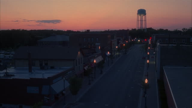 high angle long shot street lights lit along empty small town commercial street with view of water tower at twilight - dawn stock videos & royalty-free footage
