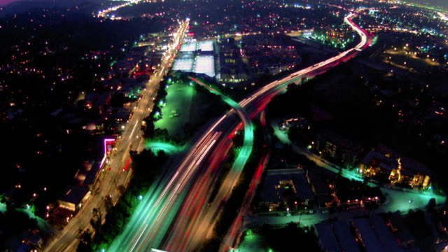 High angle long shot time lapse traffic on highways, overpasses, and streets at night / Los Angeles, California