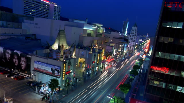 high angle long shot time lapse traffic on hollywood boulevard at night w/grauman's chinese theater in foreground / low angle - tcl chinese theatre stock videos & royalty-free footage