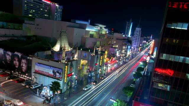 stockvideo's en b-roll-footage met high angle long shot time lapse traffic on hollywood boulevard at night w/grauman's chinese theater in foreground / low angle - tcl chinese theatre