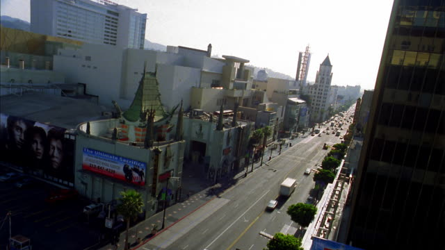 high angle long shot time lapse traffic on hollywood boulevard at dawn w/grauman's chinese theater in foreground - tlc chinese theater bildbanksvideor och videomaterial från bakom kulisserna