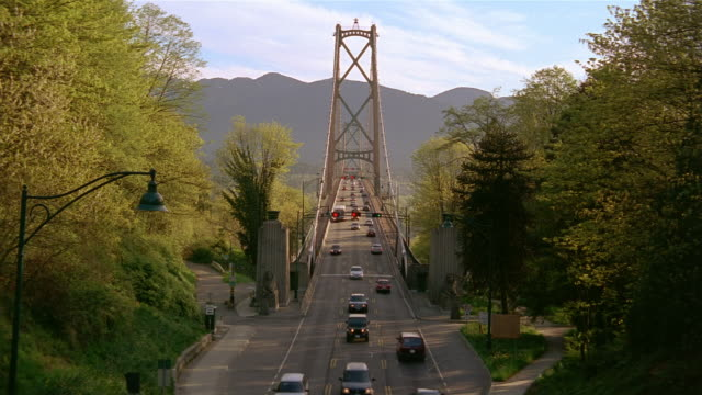 vídeos de stock, filmes e b-roll de high angle long shot traffic at one end of lions' gate bridge / vancouver - kelly mason videos