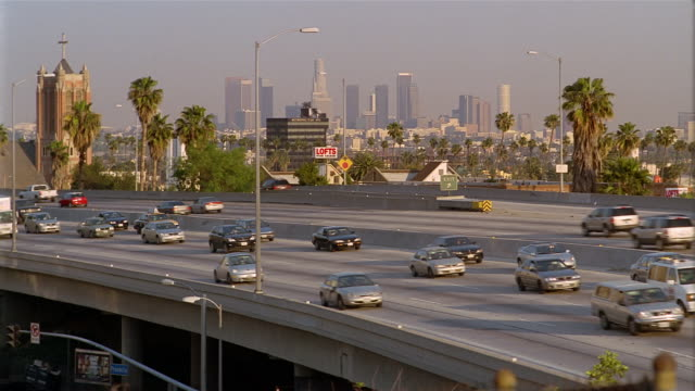high angle long shot traffic on elevated freeway / view of downtown skyline / los angeles - elevated road stock videos & royalty-free footage