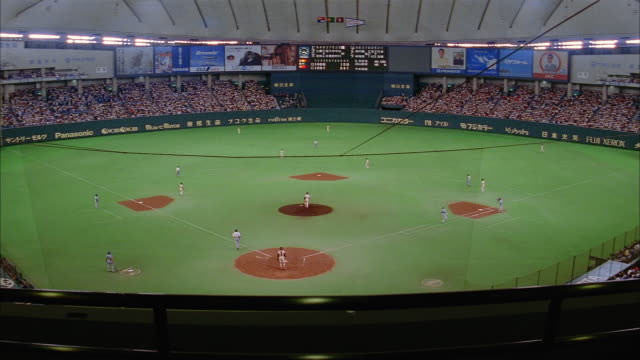 high angle long shot view of baseball game at tokyo dome /  japan - professional sportsperson stock videos & royalty-free footage
