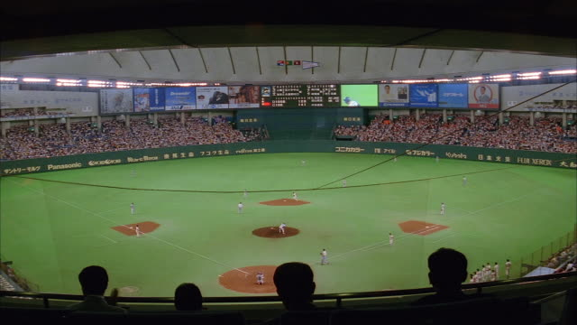 high angle long shot view of baseball game at tokyo dome / people watching in foreground /  japan - スコアボード点の映像素材/bロール