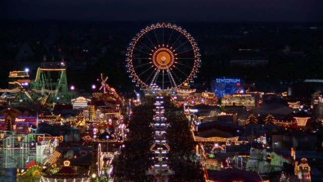 vídeos de stock, filmes e b-roll de high angle long shot view of flashing lights on ferris wheel and booths at oktoberfest at night / munich, germany - alta baviera