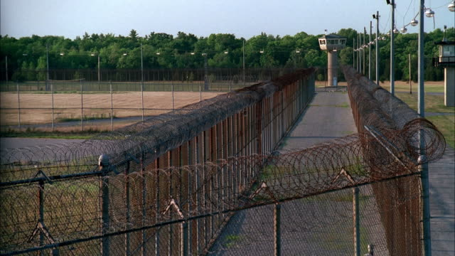 high angle long shot watchtower and barbed wire fences outside prison - prison fence stock videos & royalty-free footage