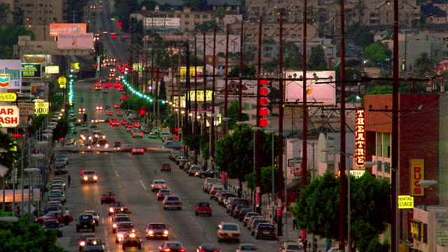 High angle long shot wide shot time lapse traffic on city street / dusk to night / Los Angeles, California