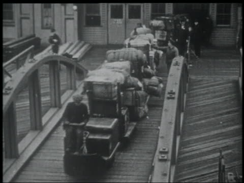 NEWSREEL high angle luggage carts moving on small footbridge / NYC
