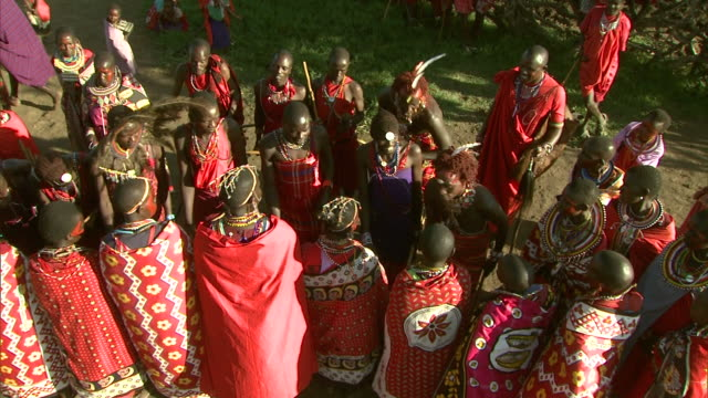 High Angle - Maasai men dance as others sing, dance, and play musical instruments in Africa / Kenya