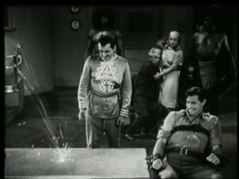 b/w 1935 high angle mad scientist doing experiment as man strapped to chair cringes - 1935 stock videos & royalty-free footage
