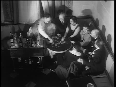 b/w 1933 high angle male bartender pouring drinks for group sitting at table / end of prohibition - anno 1933 video stock e b–roll